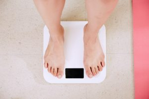 person standing on a scale weighing themself